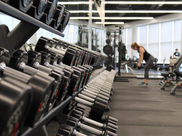 gewichten en sportende vrouw in sportschool